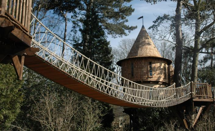 "A rope bridge connects the two levels of the ""Living the Highlife"" treehouse, designed and built by Blue Forest"