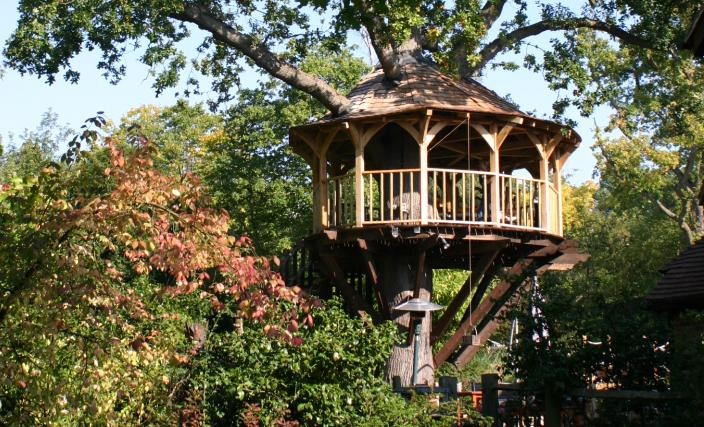 The treetop dining treehouse, built and designed by Blue Forest, has a wicker basket on a pulley for bringing up supplies.