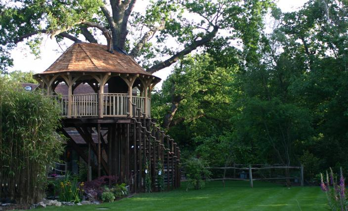 The Treetop Dining treehouse, built and designed by Blue Forest, is reached by a wide spiral staircase.