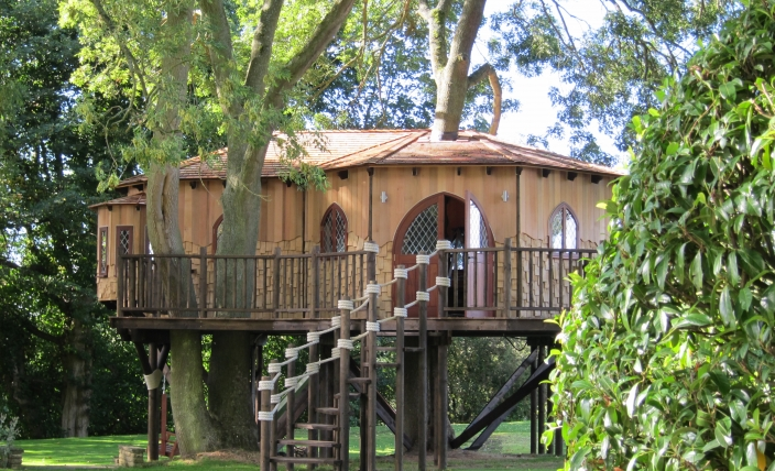 The Treehouse Office, built and designed by Blue Forest, has a winding wooden staircase with rope handrails.