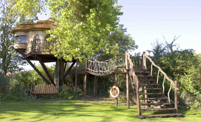 The Amerley Castle treehouse, built an designed by Blue Forest, has a swing seat to relax on.