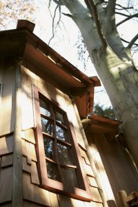 The Sleepy Hollow treehouse, built and designed by Blue Forest, has an exterior of mixed paneling and shingles.