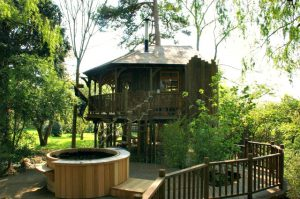The Willow Nook treehouse, designed and built by Blue Forest, has a spiral staircase with a rope handrail.