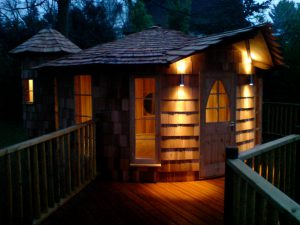 External lighting gives the Rooster treehouse, built and designed by Blue Forest, a welcoming appearance at night.