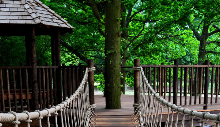 The playdeck of the Nook treehouse, designed and built by Blue Forest, is connected to the treehouse by a rope bridge.