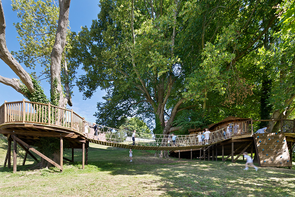 Hazelwood School Treehouse, built and designed by Blue Forest, is linked to another deck by a rope bridge.