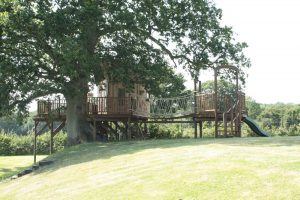 The Lookout Treehouse, designed and built by Blue Forest, is linked by rope bridge to a play deck.