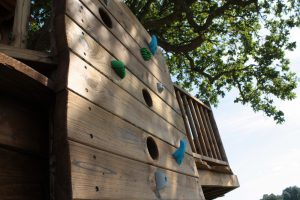 The Lookout Treehouse, designed and built by Blue Forest, has a variety of different play items including a climbing wall.