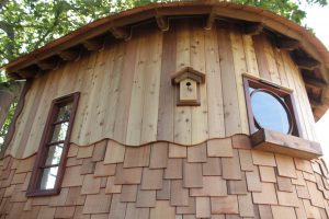 The top half of the Lookout Treehouse, designed and built by Blue Forest, is composed of planked of wood, the bottom half of shingles.