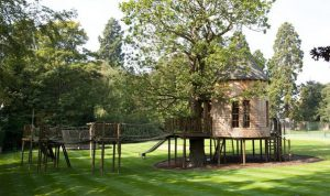 The Treetop Tower, built and designed by Blue Forest, lies in the shadow of an impressive oak tree.