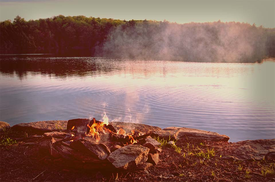 camp fire by a lake