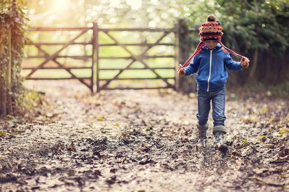 Boy walking on muddy footpath in autumn at sunrise